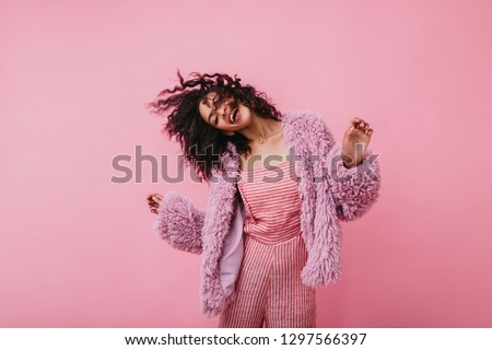 Incendiary fantastically beautiful girl in coat of eco fur moves fun. Picture of lovely lady in pink clothes