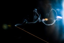 Incense burning. Aroma of smoke. Dramatic black background. Strong side light. Conceptual photography.