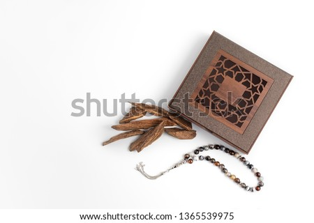 incense Chips, Agarwood, placed near wooden arabesque box with rosary beads isolated on white surface, it's name in Arabic Oud Wood used to incense Cloths, furniture and places for occasions  #1365539975