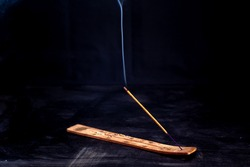 Incense stick with a wisp of smoke on a wooden stand. On a dark background