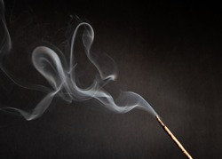 incense stick with smoke against black background