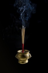 Incense sticks are burning in incense pot on the black background. The smoke during incense sticks burning for make merit. Buddhists make merit, Placing the lit incense for worship Buddha.