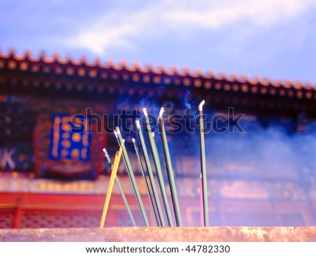 Incense sticks burning in front of an Asian pagoda. Selective focus. - stock photo
