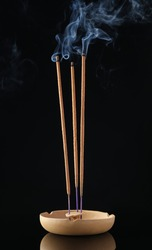 Incense sticks smoldering in holder on black background