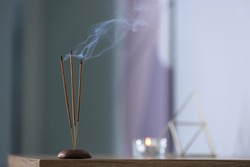 Incense sticks smoldering on table indoors, space for text