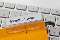 incentive plan as a term on a tab on a yellow hanging file on a computer keyboard