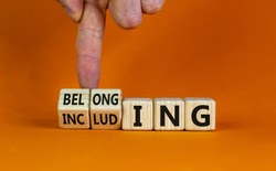 Including or belonging symbol. Businessman hand turns cubes and changes the word 'including' to 'belonging'. Beautiful orange background. Business and Including or belonging concept. Copy space.