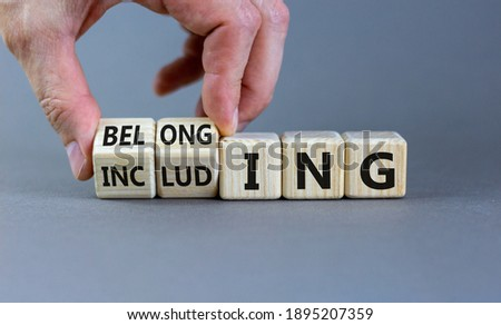 Including or belonging symbol. Businessman hand turns cubes and changes the word 'including' to 'belonging'. Beautiful grey background. Business and Including or belonging concept. Copy space. ストックフォト ©