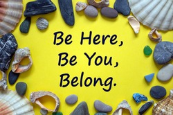 Inclusion and belonging symbol. Words be here, be you, belong on a beautiful yellow background. Sea stones and seashells. Business, inclusion, belonging and belong here concept. Beautiful background.