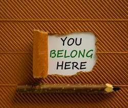 Inclusion and belonging symbol. Words 'You belong here' appearing behind torn brown paper. Beautiful brown background. Business, better inclusion and belonging concept. Copy space.
