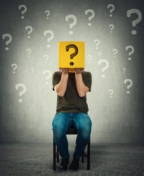 Incognito young man seated on a chair holding a yellow box with question mark instead of head. Introvert person anonymity concept hiding identity behind a mask. Social issue, shy guy covering face.