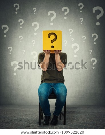 Incognito young man seated on a chair holding a yellow box with question mark instead of head. Introvert person anonymity concept hiding identity behind a mask. Social issue, shy guy covering face. Сток-фото ©