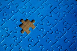 Incomplete blue piece puzzle with a missing piece over a wooden table