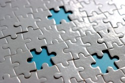 incomplete white jigsaw puzzle, missing puzzle pieces showing blue background.
