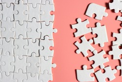 incomplete white jigsaw puzzle with plain pink background