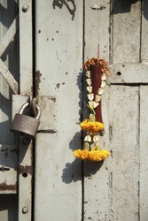 Incongruous glimpse of faith: old metal door, lock, and flower garland and burned incense stick
