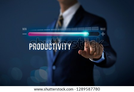 Increase productivity concept. Businessman is pulling up progress bar with the word PRODUCTIVITY on dark tone background. #1289587780