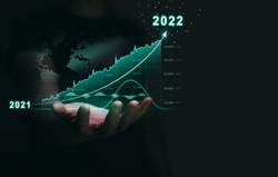Increasing revenues and business in the new year 2022.   Businessman holding growth  arrow graph corporate future growth year 2021 to 2022.  Development to success.