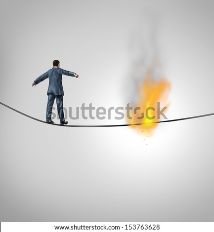 Increasing risk business concept and metaphor for overcoming adversity and dangers  following a risky strategy on the line as a businessman walking on a burning hazardous high wire thread.
