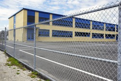 Increasing security of an old small school by restricting access with a gate or wire mesh fence courtyard asphalt playground.