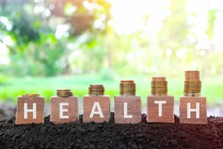 Increasing stack of coins with word health in wooden blocks. Invest on health, save and healthcare cost growth and insurance concept.