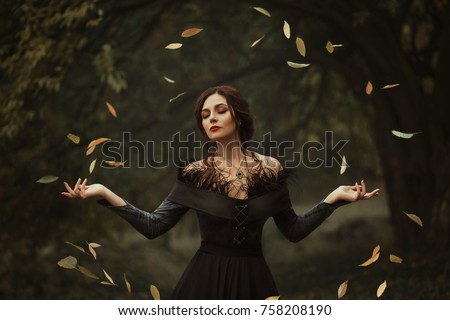 Incredible, amazing, seductive girl, in a  dress , magic rotates the leaves. The background is fantastic autumn. Artistic photography.