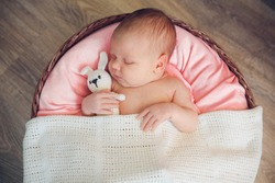 Incredible and sweet newborn baby sleeps in round basket with a toy hare (rabbit) on a wooden dark background