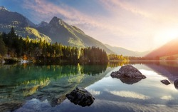 Incredible Colorful Sunset at Mountain Valley. Fairy tale lake Hintersee. Awesome alpine highlands in sunlit. Amazing nature landscape with Picturesque Sky. Beautiful locations of the World. Bavaria
