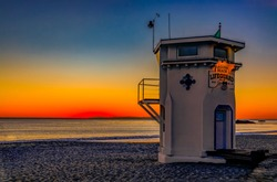 Incredible colors of sunset in Laguna Beach, famous tourist destination in California, USA with a lifeguard station in the foreground
