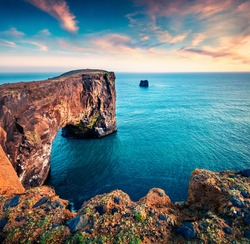 Incredible evening view of Dyrholaey arch. Dramatic summer sunset in Dyrholaey Nature Reserv, south coast of Iceland, Europe. Beauty of nature concept background.