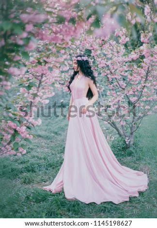 Incredible, gentle elf in a luxurious, gently pink dress strolls in the spring, blooming sakura and cherry orchard. Princess with long curly hair that adorns a flower wreath. Vanilla color art photo #1145198627