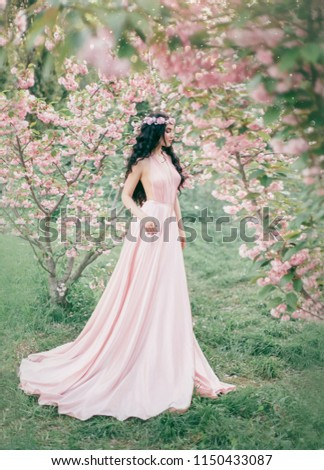 Incredible, gentle elf in a luxurious, gently pink dress strolls in the spring, blooming sakura and cherry orchard. Princess with long curly hair that adorns a flower wreath. Vanilla color art photo #1150433087
