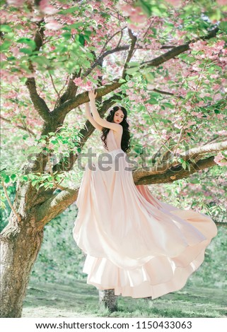 Incredible, gentle elf in a luxurious, gently pink dress that flutters in the wind. The princess with long curly hair sits on a branch of a blooming tree, like a bird. Vanilla color art photo #1150433063