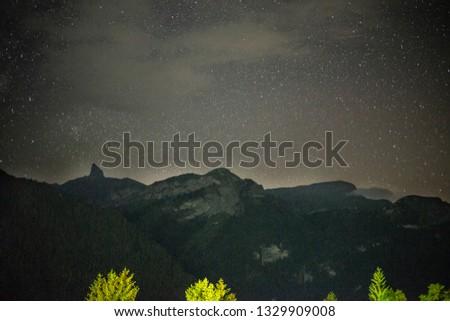 Incredible night view in Swiss Alps. Star trails moving in blue sky. Zermatt resort location, Weisshorn, Switzerland.Landscape astrophotography background. #1329909008