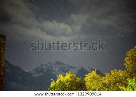 Incredible night view in Swiss Alps. Star trails moving in blue sky. Zermatt resort location, Weisshorn, Switzerland.Landscape astrophotography background. #1329909014