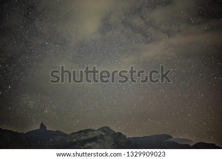 Incredible night view in Swiss Alps. Star trails moving in blue sky. Zermatt resort location, Weisshorn, Switzerland.Landscape astrophotography background. #1329909023