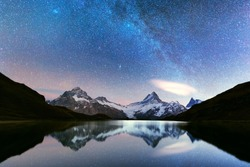 Incredible night view of Bachalpsee lake in Swiss Alps mountains. Snowy peaks of Wetterhorn, Mittelhorn and Rosenhorn on background. Grindelwald valley, Switzerland. Landscape astrophotography