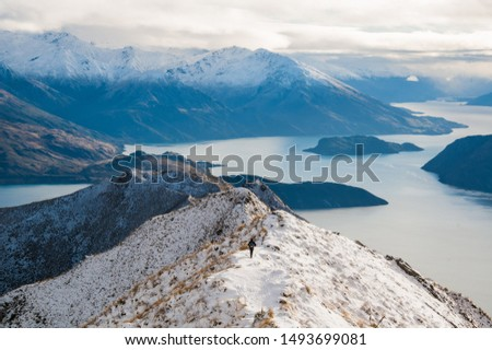 Incredible peaks in Wanaka (New Zealand). Winter mountain landscape with fresh snow, ice, and autumn colors. Some hikers around may also be present. Roys Peak Track.