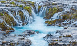 Incredible view of Bruarfoss Waterfall.  The 'Iceland's Bluest Waterfall.' Blue water flows over stones. Midnight sun of Iceland. Visit Iceland. Beauty world.