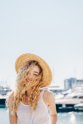 Incredible young girl with blond curly hair developing from the wind with the straw hat on her head in the white top against the sea, smiles sweetly and winks