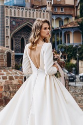 incredibly charming bride poses for a photo in a sophisticated wedding dress on the background of old Georgian city Tbilisi