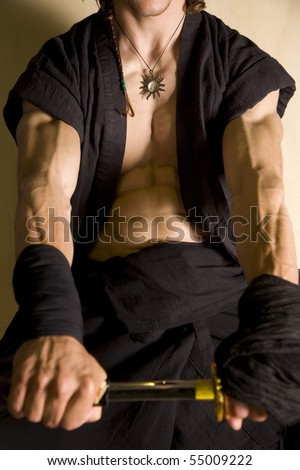 incredibly muscular body of a samurai warrior with katana or samurai sword in a kneeling pose