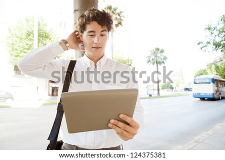Indecisive businessman scratching his head while using a tablet device, standing in a wide city avenue with traffic and public transport, outdoors.