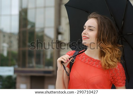 Independence, confidence, elegance concept. Slim girl walking down the street of the city under an umbrella