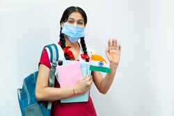 Independence Day (15 august) - happy Indian teenager girl in school uniform with braided hair  holding books, waving hands, wearing protective surgical face mask of Indian flag.