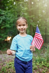 Independence Day celebration. Two pretty kids holding American flags in the park at summer to celebrate national holiday, family celebration, outdoor lifestyle