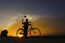 independence Day concept - Silhouette of young local boy on paddy field holding a Malaysian flag during sunset
