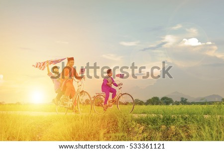 Independence Day concept - Two happy young local boy riding old bicycle at paddy field holding a Malaysian flag #533361121