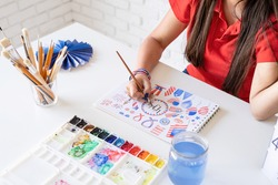 Independence day of the USA. Happy July 4th. Beautiful woman drawing a watercolor illustration for Independence day of the USA.