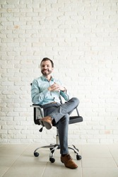 Independent business man sitting on a chair with his leg crossed against a brick wall